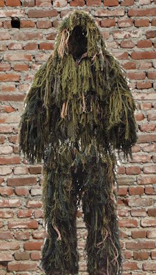 A Ghillie suit against a brick wall background