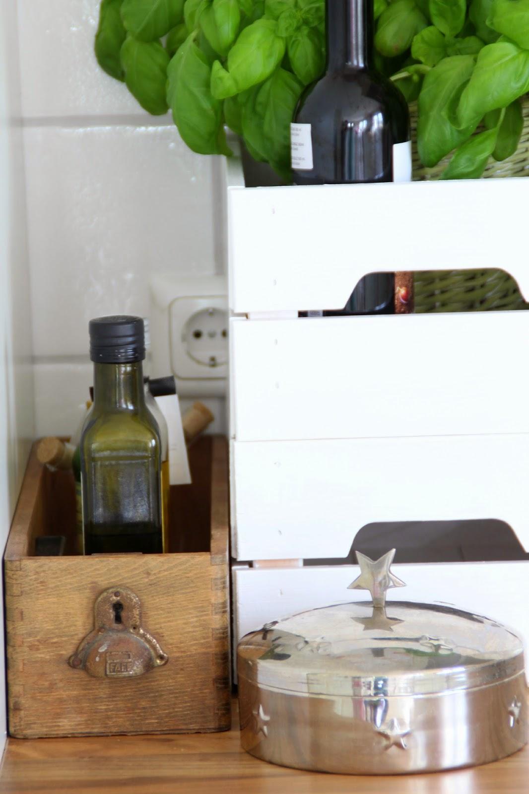 Links kleine braune Schublade als Küchenutensio für kleine Ölflaschen rechts Kiste Knagglig als Basilikumübertopf