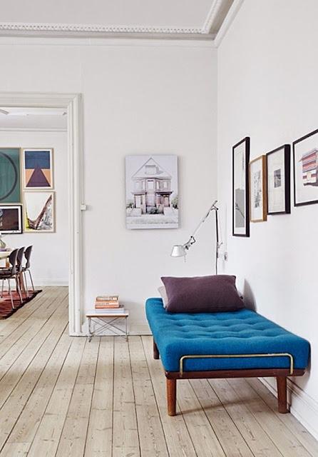 en blå daybed og rigeligt at kunst, billedvægge og gallerivægge