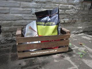 cajón de verduras, bolsa de carbón y papel de diario para prender fuego