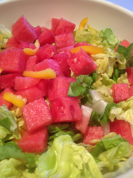 Image of the vibrant watermelon, green onion and yellow peppers atop the butter lettuce. This was taken just before the avocados are added and the salad is tossed.
