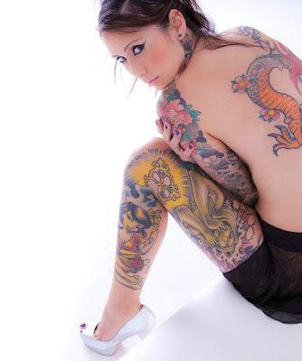 Mulher tatuada nas pernas e braço
