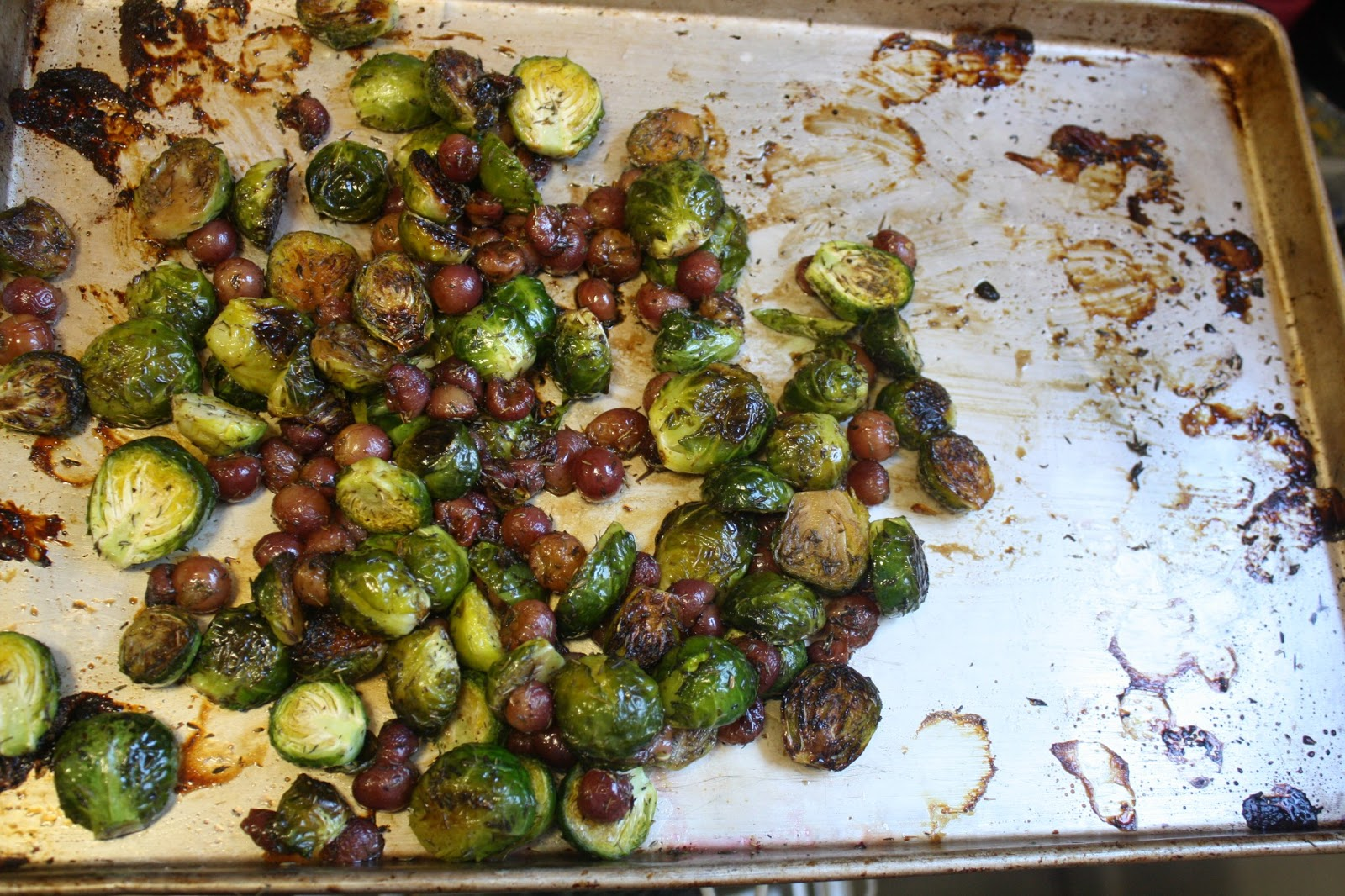 and pepper tossed brussels sprouts and grapes on a baking sheet