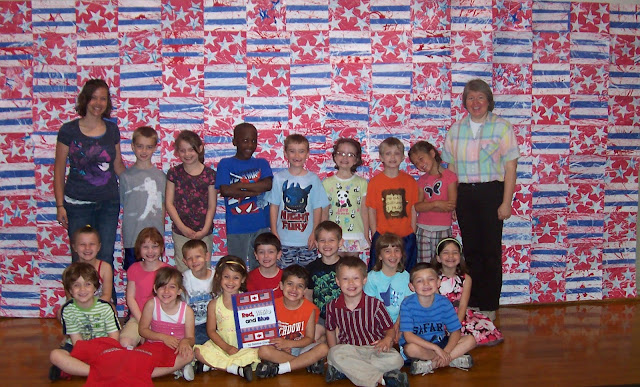 "photo of: Kindergarten Children Pose in front of their Collaborative Quilt Project, for ""Red, White and Blue"" picture book by Debbie Clement"