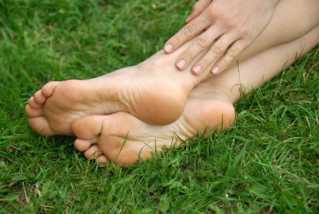 Woman healthy feet and hand over green grass outdoor. The network of nerves that stimulate your feet are the same network that are present in your genitals.