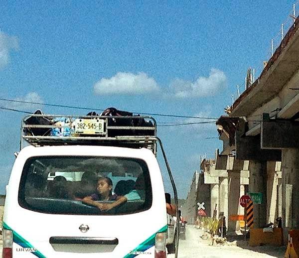 Una niña viaja en pequeño autobus junto  a la carretera que une Campeche y Mérida.