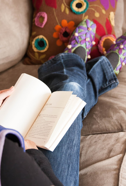woman in colored slippers reading a book
