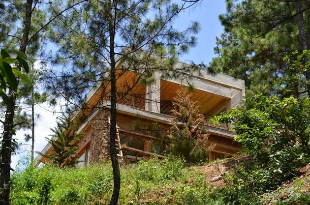 Rumah miring beratap rumput hijau