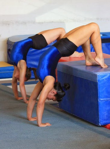 two gymnasts in an upside-down pose