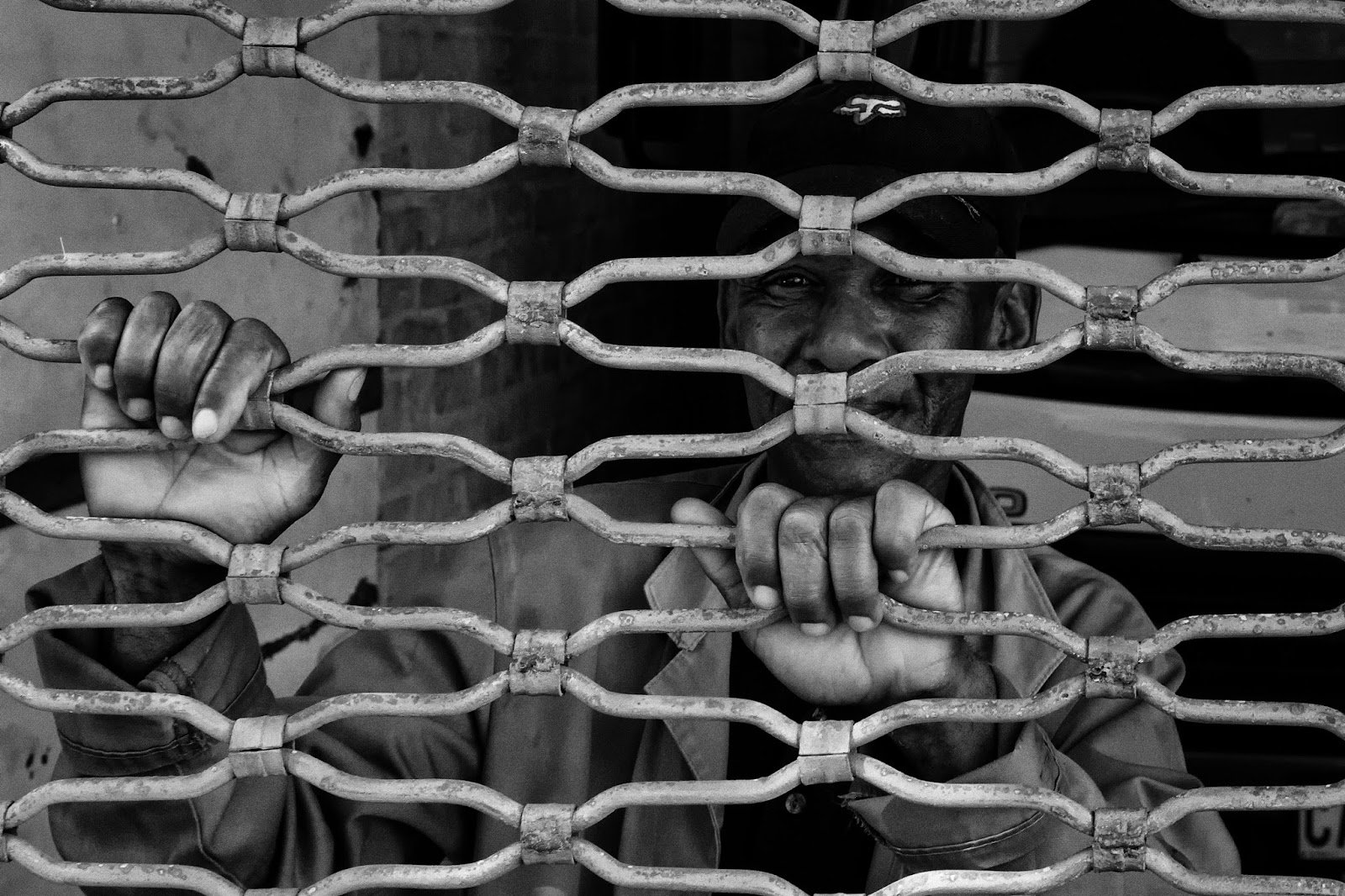 A man smiles with his hands holding on to the security bars in front of him