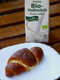 Hörnchen auf dem Teller, Biomilch im Tetrapack, beides auf dem Tisch