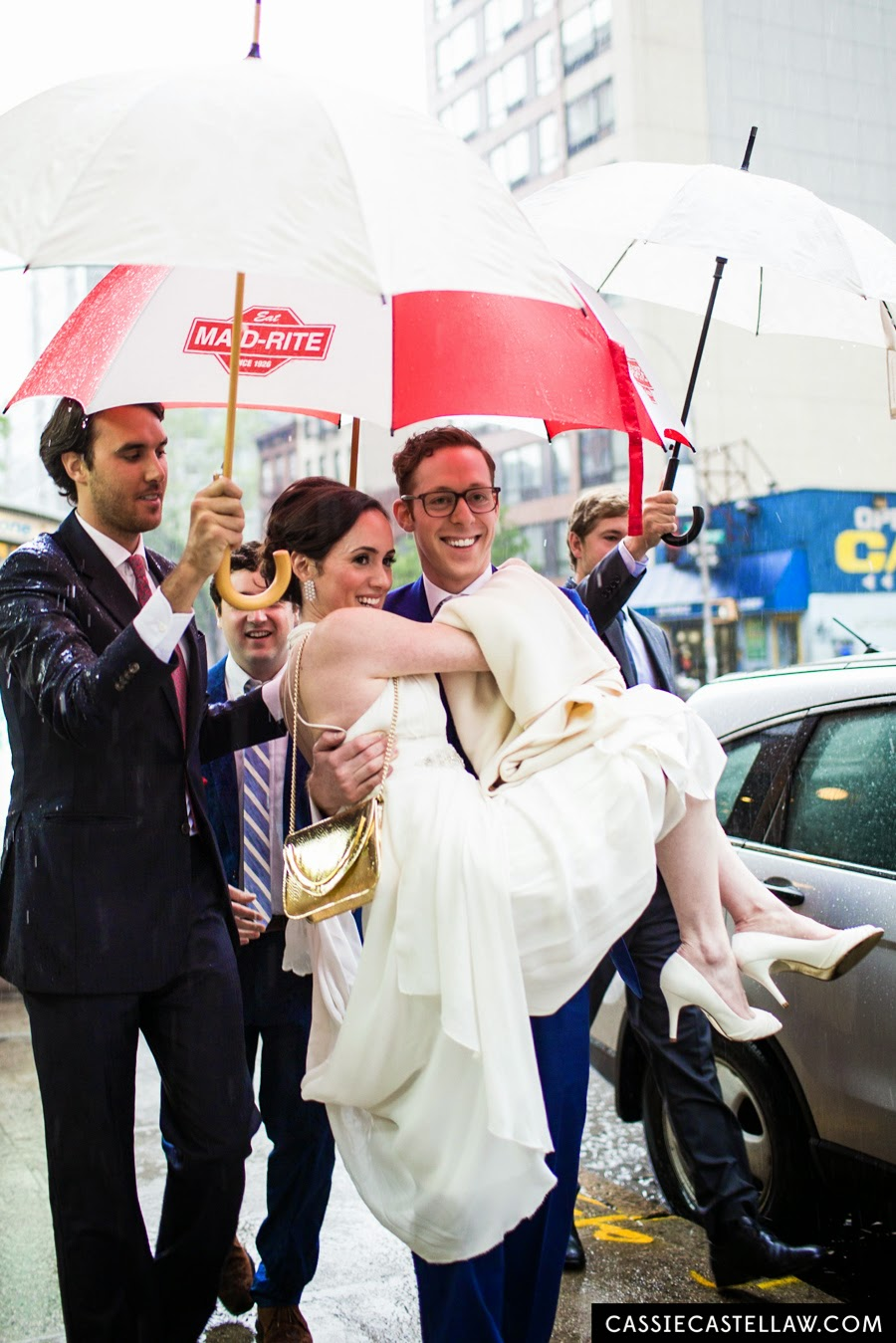 Bridal party with umbrellas sheilding groom carrying bride in the pouring rain on their wedding day. NYC Lifestyle wedding photography by Cassie Castellaw. www.cassiecastellaw.com
