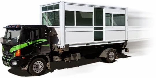 Lastbilsbild med container på flaket.Hål för gaffeltryck syns i nedansidan av balk.