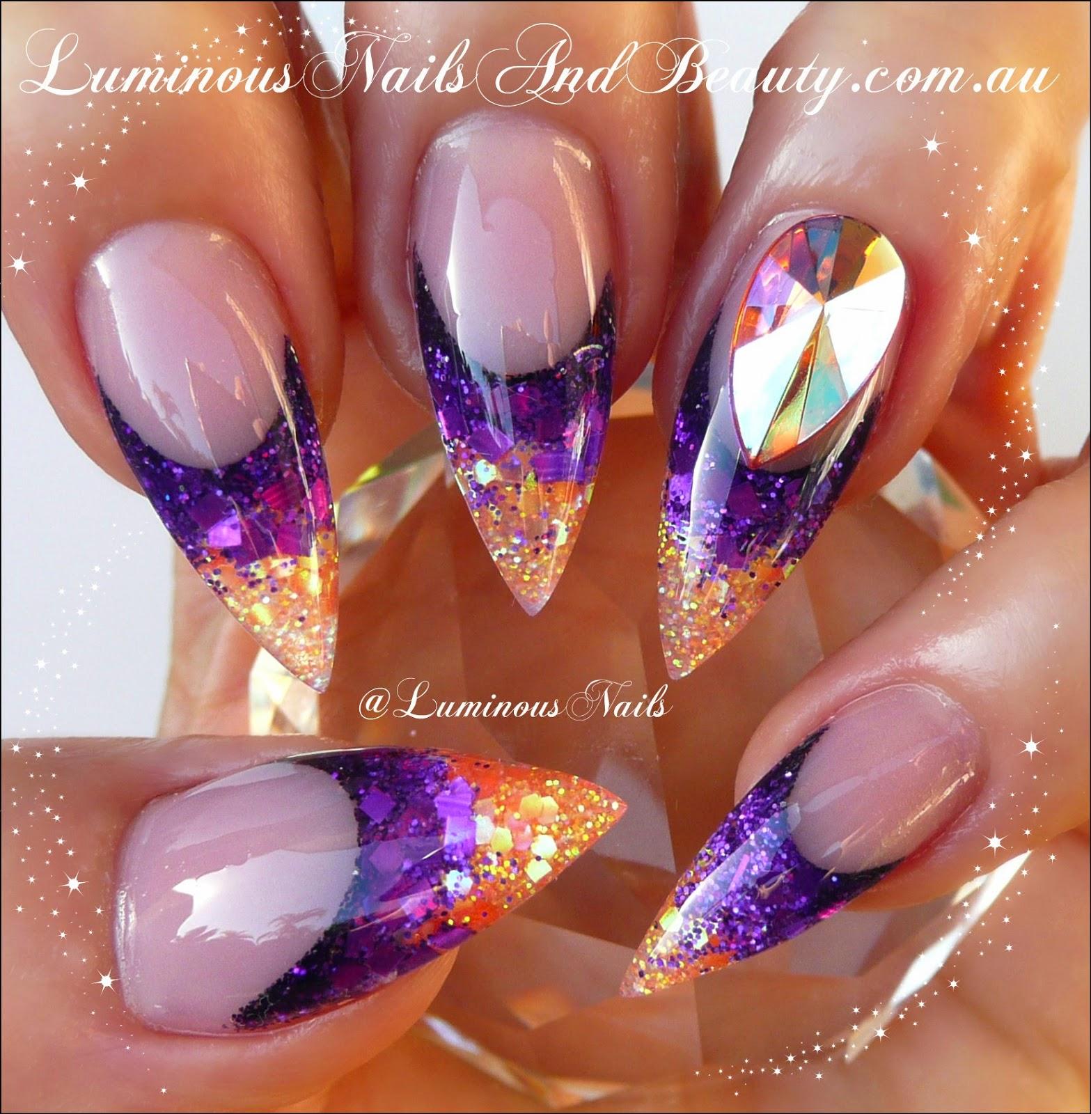 luminous nails: purple & orange acryic nails with big bling