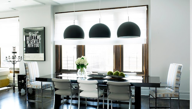 Sleek modern kitchen with three black dome pendant lights hung over a black dining room table surrounded by upholstered chairs with higher back chairs at the head of the table.