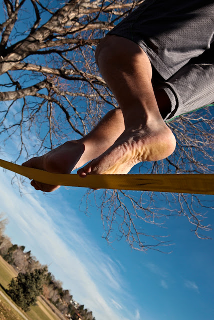 A guy with grass stained feet walking on a Gibbon Slackline.
