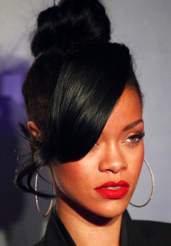 Rihanna siyah saçlarını gergin tepe topuz saç modeli yaptırmış ve uzun kahküllerini sağ yanına ayırmıştır.
