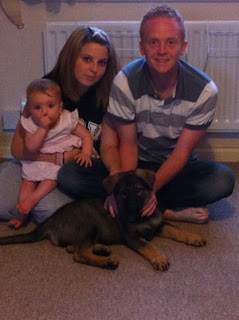 Mum dad baby in a family group sitting on floor with their German shepherd puppy.