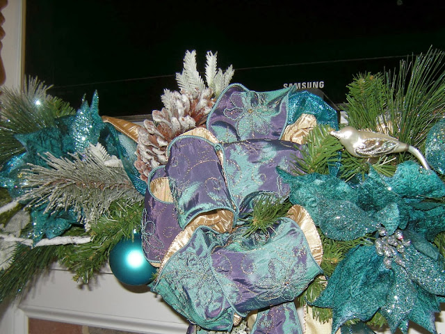 Flocked branches and pine cones on a teal and gold Christmas garland.