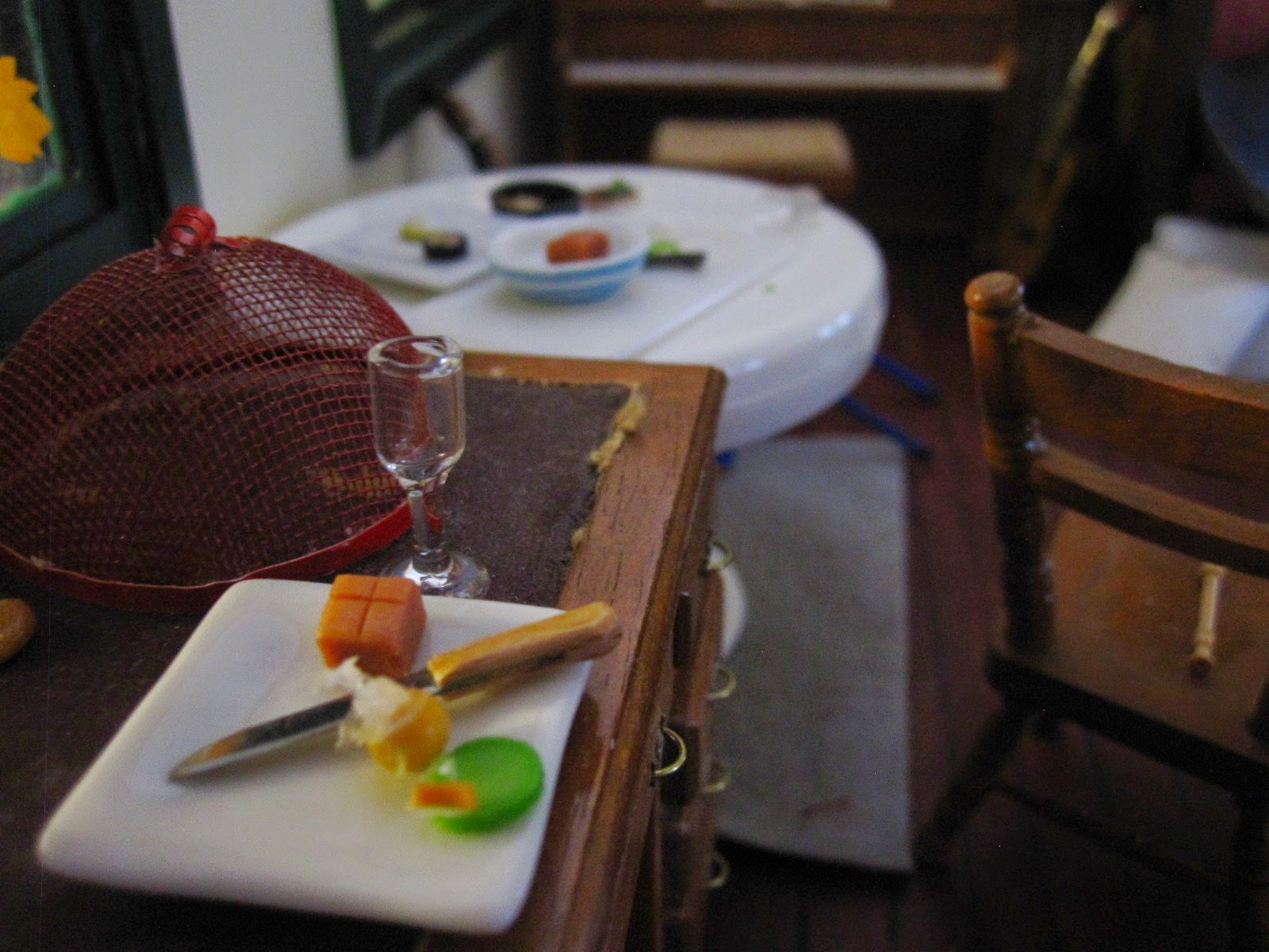 Modern dolls' house miniature post-party scene with empty serving platters and plates on tables.