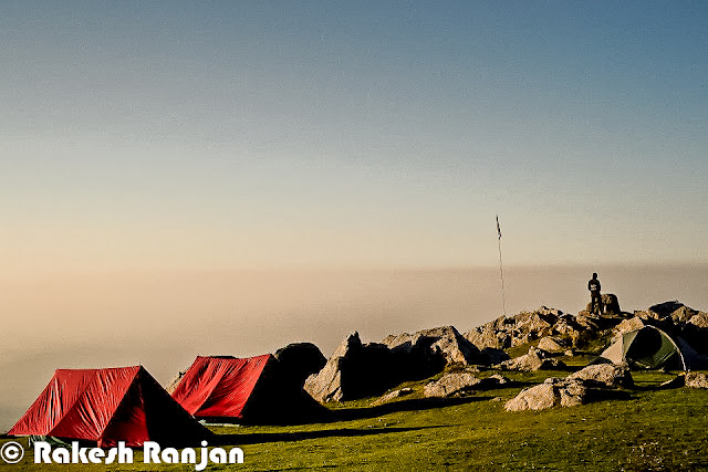 Triund is one of the popular treks in Himachal Pradesh. This is counted in moderate treks, although many of the trekkers consider it simple trek. This Photo Journey shares wonderful series of photographs by Rakesh Ranjan, who has done this trek many times. Let's check out this Photo Journey and enjoy the trek with Rakesh Ranjan !Triund is just 10 kilometers from Bhagsu Nag which is now very famous among  foreigner tourist as a trekking paradise. Triund is name of a ridge in Dhauladhar Himalayas... Reaching Triund is very easy for people coming to Mcledoganj and Dharmshala. Accommodation at Triund is available in the rest house of Forest Department, but water has to be fetched from a distance of about 2 kilometers. Most of the times trekkers prefer to stay in tents. Many local companies arrange trekking facilities for trekkers & tourists. Although many of the trekkers take their stuff with them.  Triund lies at the feet of the perpetually snow covered Dhauladhar mountain ranges at the height of three thousands meters. It's around 20 kilometers from Dharmshala Town. The snow line starts at Ilaqa which is at 3300 feet, 5km from Triund.A photograph showing sunset moments from top at Triund !Triund is a popular picnic and trekking spot around Dharmshala/Mcleodganj. The tracks from Rawa, Dal Lake, Dharamkot and Bhagsunag meet at a ridge known as Galu temple (2130 meters) which has a small shrine and water point.A wonderful photograph by Rakesh Ranjan which looks quite similar to what we have seen in Windows-XP wallpapersHimalayas is very beautiful but my main emphasis to come in this area can be Yoga & Meditation...The trek to Triund is quite easy as compared to other treks and first timers can manage doing this trek. Some of the trekkers also like to move ahead to Ilaka, as path is a little treacherous in some spots can be more adventurous.A herd of Sheeps around Triund Trek !A View of Mcleodganj & Dharmshala towns from triund Trek in Himachal Pradesh !Folks who plan to 
