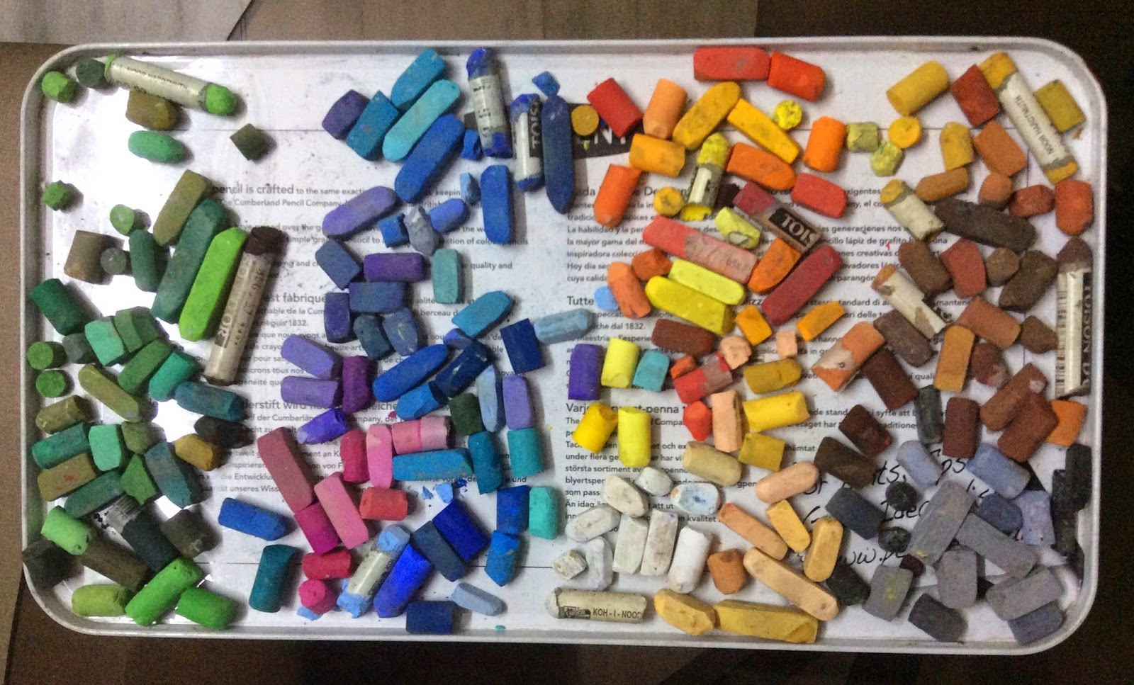 Arranging and organising different brands of soft pastels as per similar colours