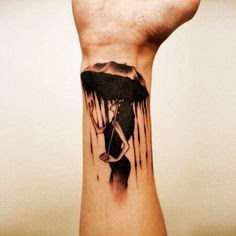 Black ink lady and umbrella tattoo on wrist