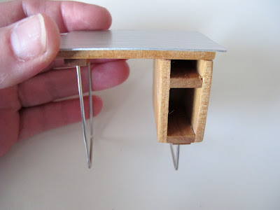 Hand holding a dolls' house miniature mid-century-modern desk in wood and metal.