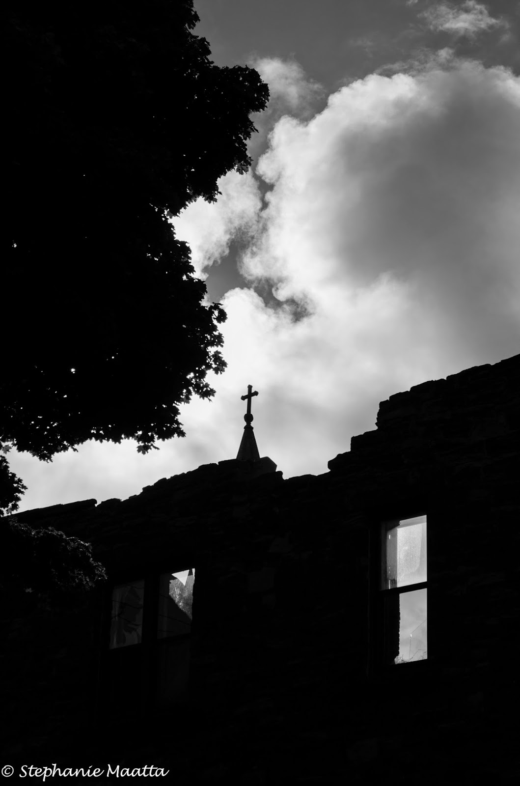 building with caved in roof and church steepl in background, image in black and white