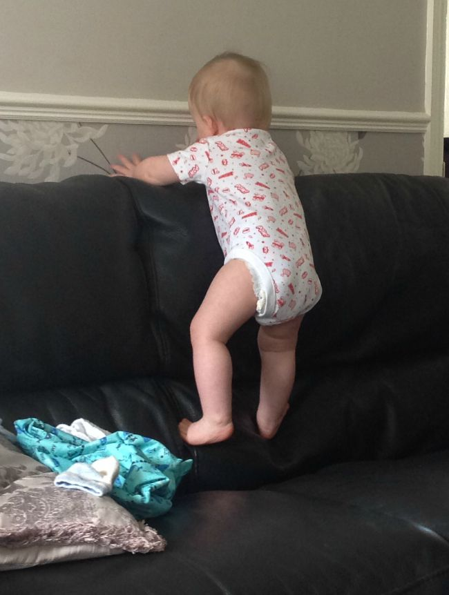 baby climbing the back of a black sofa