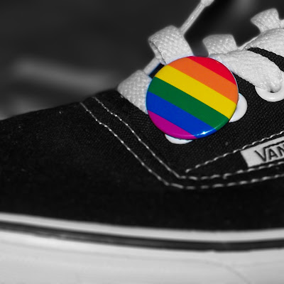 A rainbow flag badge on a Vans shoe.