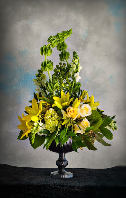 Isha Foss Events roses, lilies, snapdragons, hydrangea, seeded eucalyptus in bronze planter