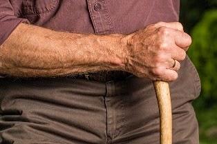 la mano di un anziano tiene un bastone