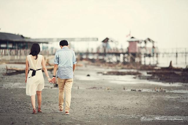 back of couple walking sand