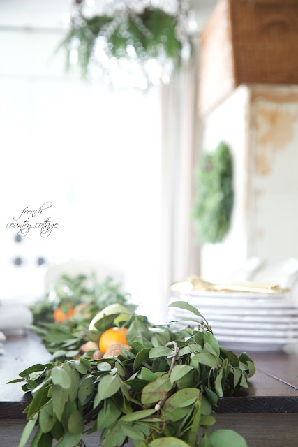 Dining table with fresh greens and citrus fruit as a centerpiece