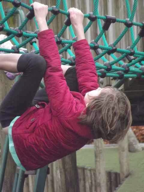 girl dangling from climbing frame