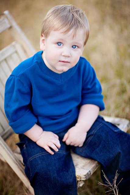 Beautiful blue eyed boy smirks at camera of Tucson Photographer