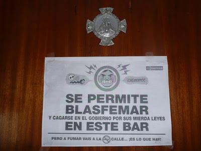 """Fotocopia pegada en una puerta debajo de una medalla del corazón de Jesús, en la que puede leerse: """"Se permite blasfemar y cagarse en el gobierno por sus mierda leyes en este bar. Pero a fumar vais a la [tachado] calle.... ¡Es lo que hay!""""."""