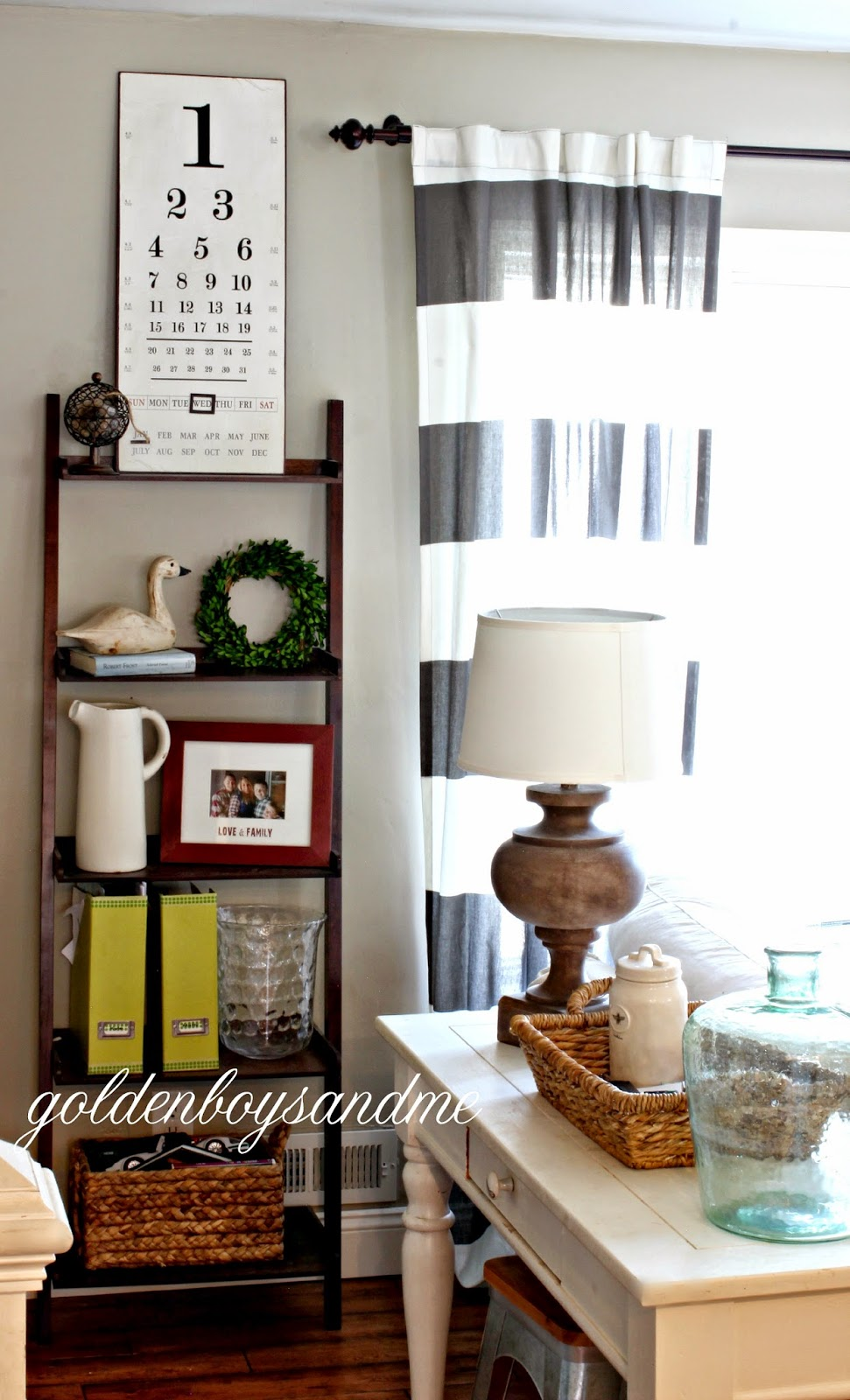 ladder style bookshelf in neutral living room with magnetic eye chart perpetual calendar-www.goldenboysandme.com