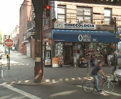 "A red brick building with a music store on the first floor and a sign above the store in Spanish reading ""A1 Ginecologica"""