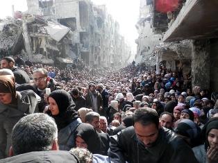 Refugiados palestinos fazem fila para recebr comida no Yarmouk