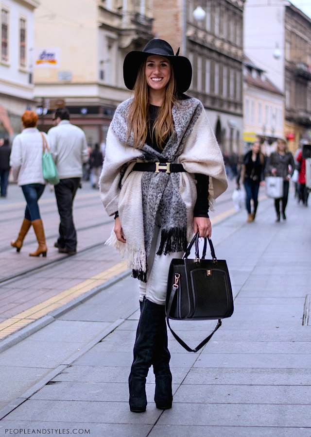 Floppy hat, Hermès belt, black bag, knee high black boots, shawl/cape. Great street style look