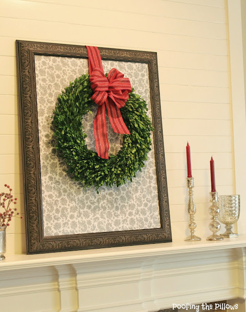 Christmas mantel with boxwood wreath and a beautiful red bow.