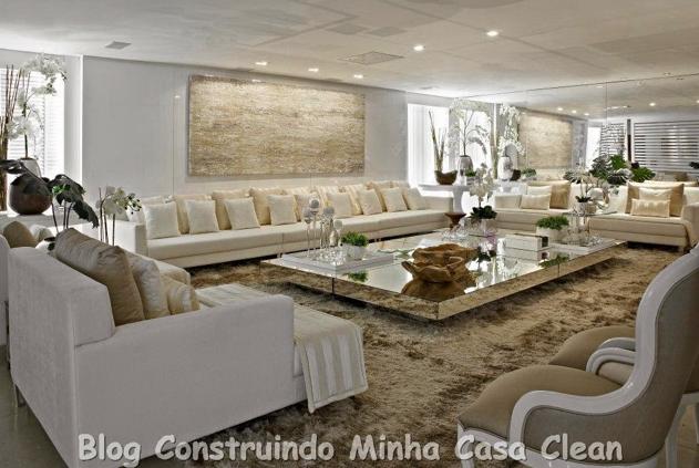 Sala de estar ampla branca com sofás creme, branco e poltronas bege