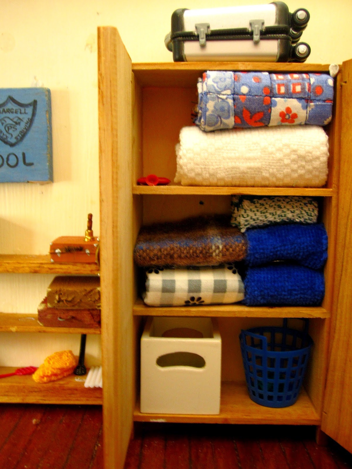 Modern dolls' house miniature cupboard containing spare linen and storage boxes.