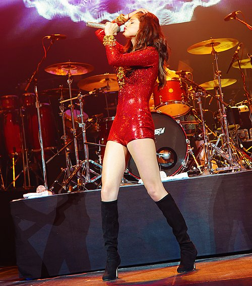 Fashionista and singer Selena Gomez style outfits red sequin romper on stage.