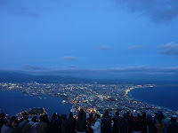 Night / Twilight view of Hakodate and it's sparkling lights and ocean from Mt Hakodate with crowd of people in the foreground