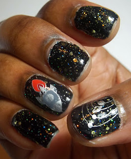 Space themed manicure featuring  black nails with gold and holographic glitter, stamped with orbiting planets in silver on the thumb, and a grey and silver rocket ship with red and orange flames trailing it is stamped on the ring finger.