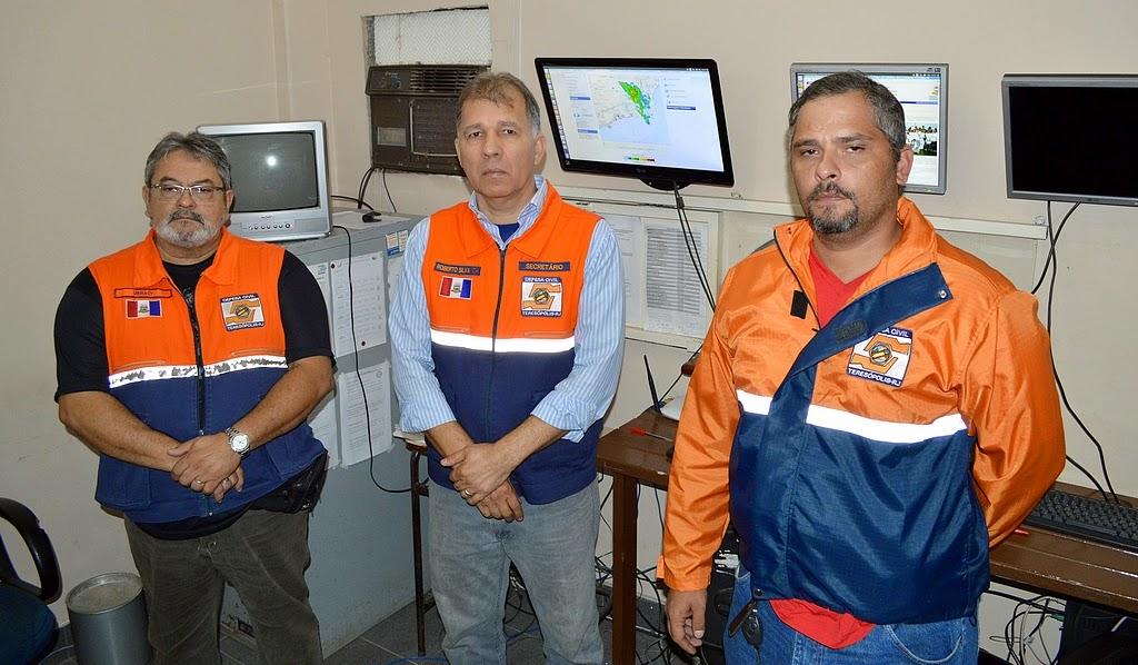 Secretário de Defesa Civil, coronel Roberto Silva, entre os agentes Ubiracy Pinto e Igor Cruz no Centro de e Comunicação: condições do tempo monitoradas e boletins repassados à população