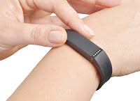 Health wearables: A woman is adjusting her Fitbit